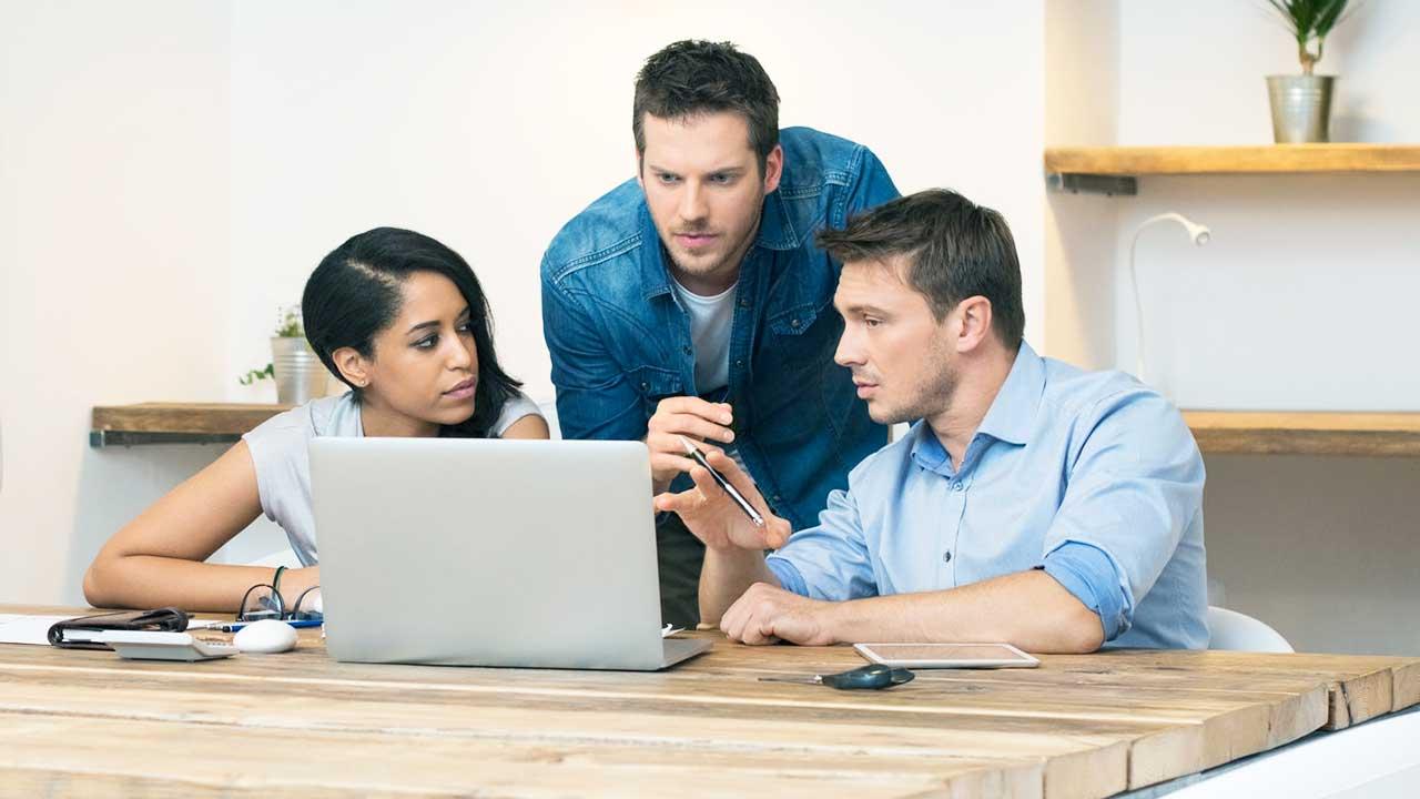 Eine Frau und zwei Männer diskutieren an einem Büroarbeitsplatz mit Computer