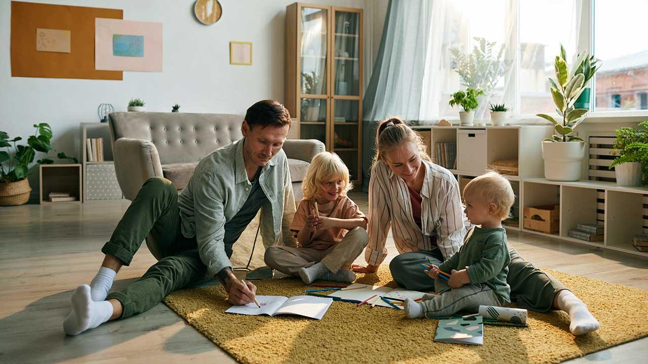 Eltern und Kinder sitzen zusammen auf dem Boden des Wohnzimmers