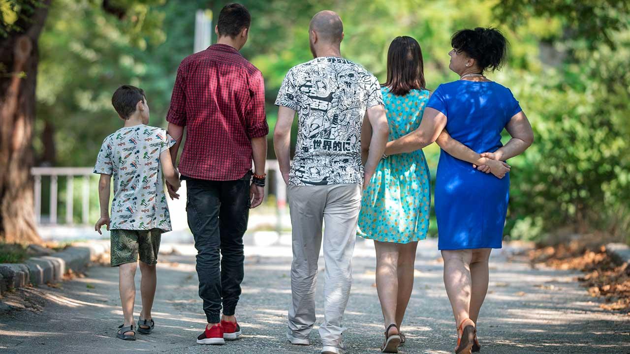 Rückansicht auf eine fünfköpfige Familie, welche spaziert