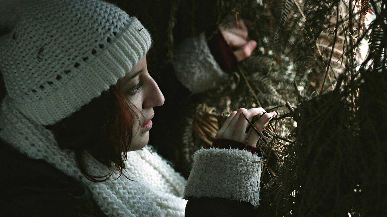 Frau blickt zwischen den Zweigen durch