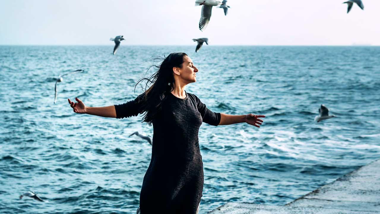 Frau steht mit ausgestreckten Händen am Meer