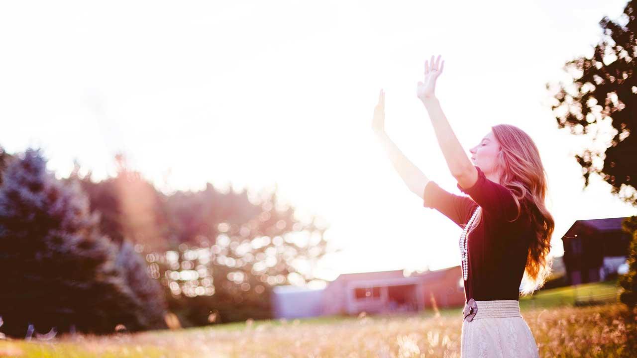 Frau streckt Hände nach oben und konzentriert sich auf Gott