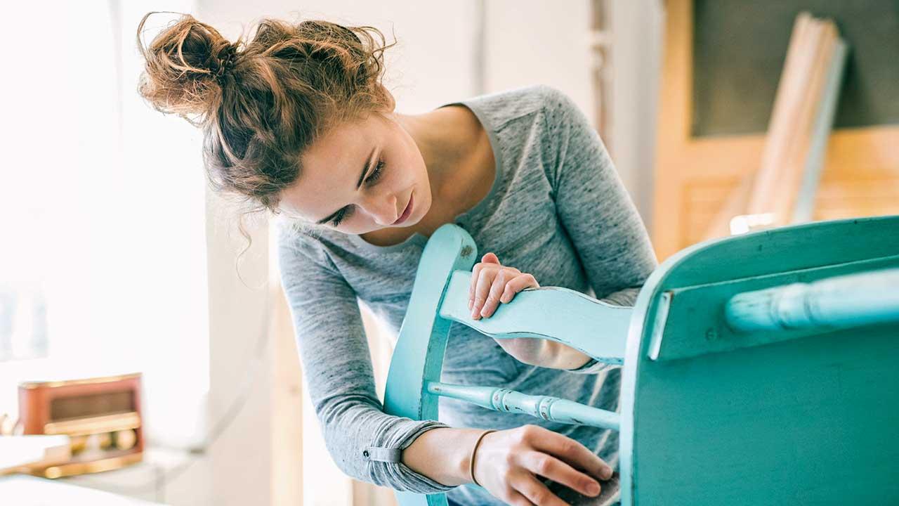 Junge Frau repariert einen türkis Stuhl