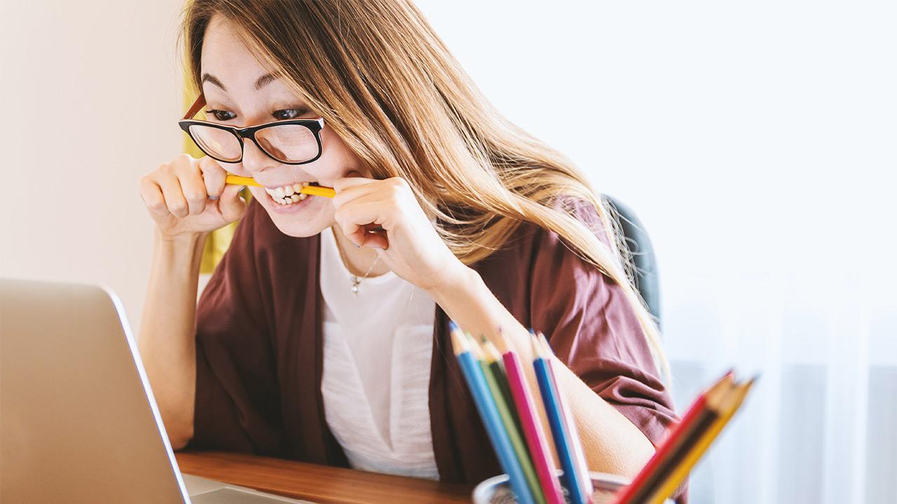 Eine Frau beim Lernen. Sie beisst auf einen Stift.