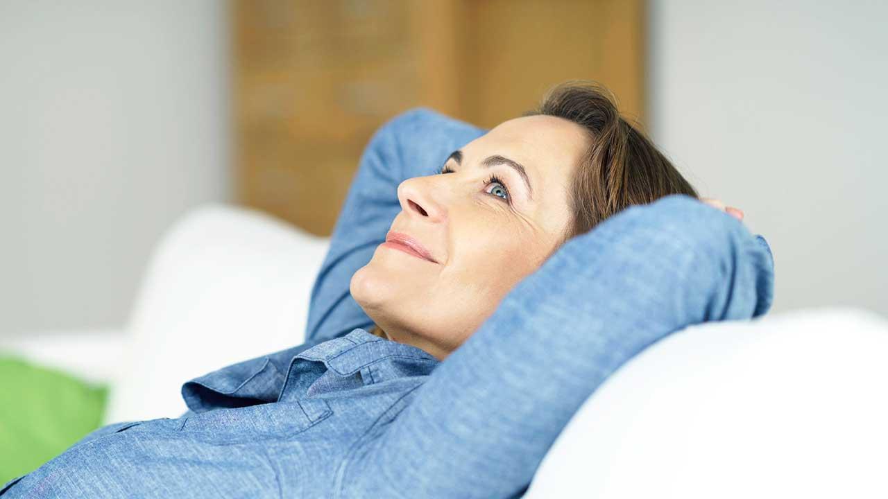 Frau liegt lächelnd auf einem Sofa und blickt nach Oben