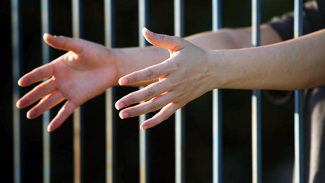 Ausgestreckte Hände aus der Zelle
