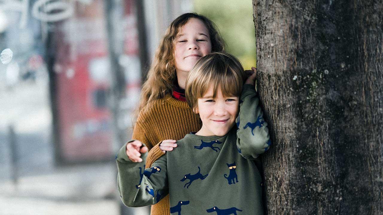 Schwester und Bruder stehen neben einem Baum
