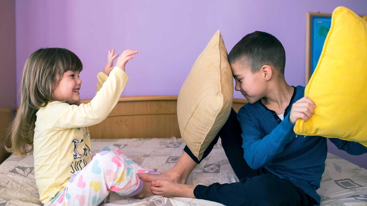 Zwei Geschwister machen eine Kissenschlacht