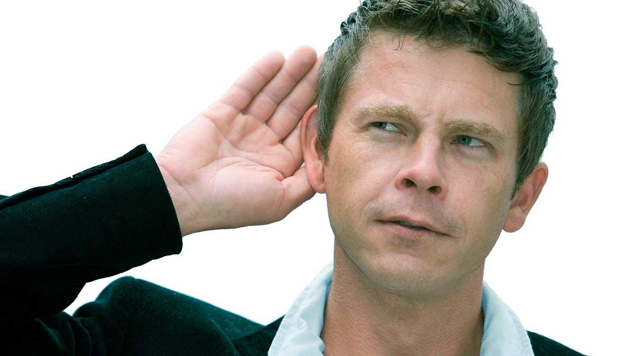 Mann hält Hand an Ohr und lauscht konzentriert