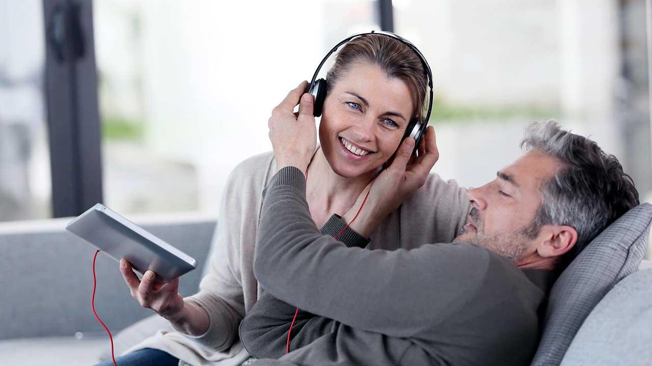 Paar hört auf einem Sofa Musik oder Radio