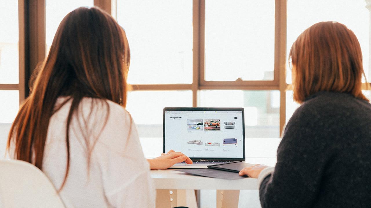 Zwei Frauen vor einem Laptop-Bildschirm.