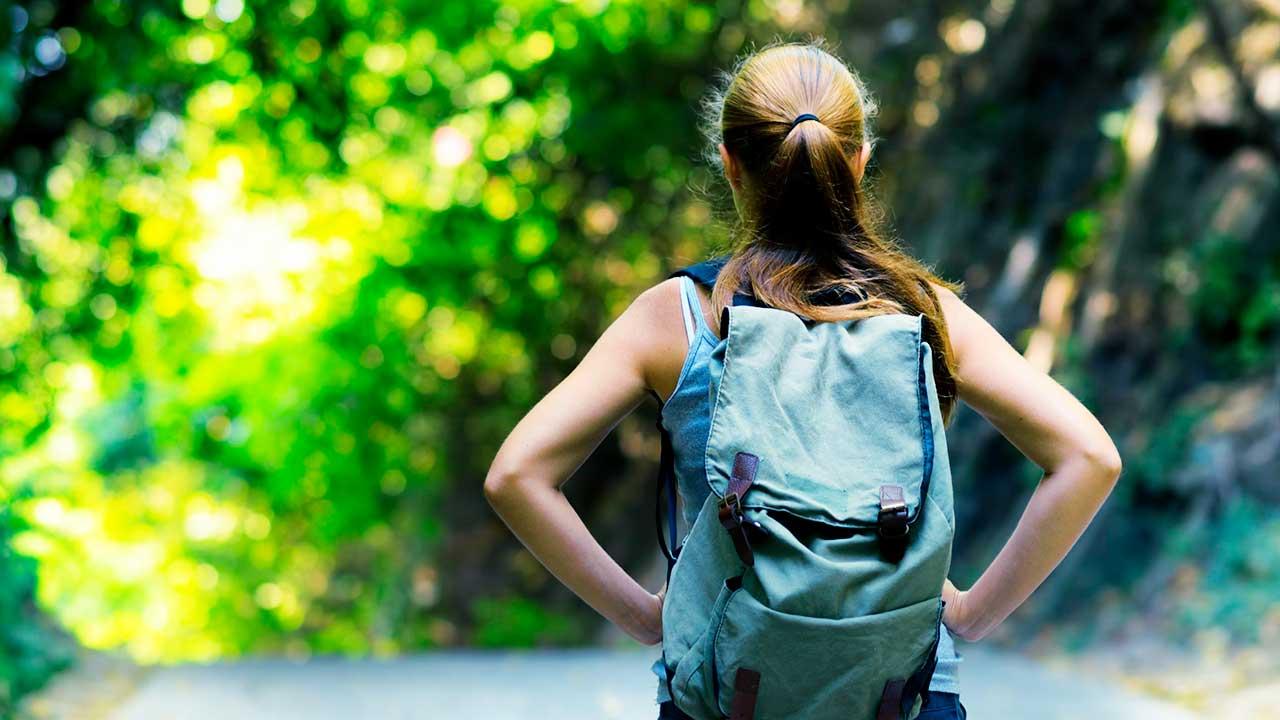 Rückansicht auf eine junge Frau, welche wandernd unterwegs ist