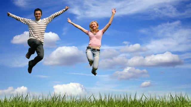 Junges Paar macht Freudensprünge in die Luft